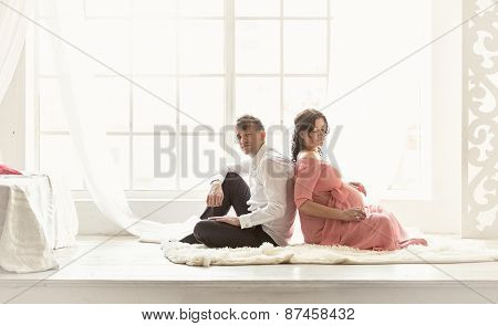Pregnant Couple Sitting Back To Back On Floor Against Big Window