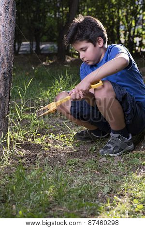 Little boy digging with his toy shovel