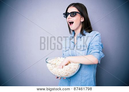 Surprised woman in cinema glasses holding bowl with popcorn over gray background. Looking away