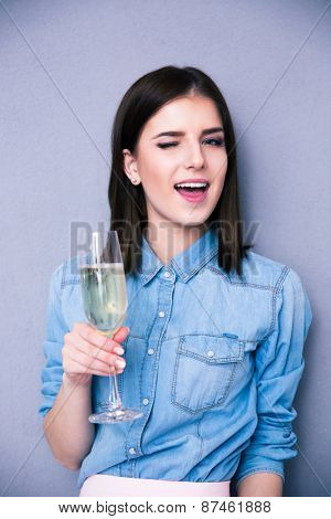 Beautiful young woman holding glass of champagne and winking. Standing over gray background. Looking at camera
