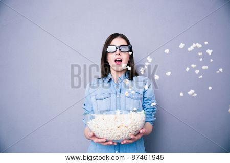Amazed cute woman in cinema standing with bowl of popcorn over gray background