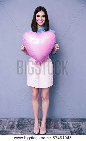 Full length portrait of a smiling pretty woman holding heart shaped balloon over gray wall. Looking at camera