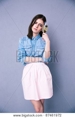 Sad woman holding glass of champagne over gray background. Waring in pink skirt and shirt. Looking away