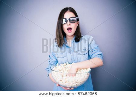 Surprised pretty woman in cinema glasses eating popcorn over gray background. Looking at camera