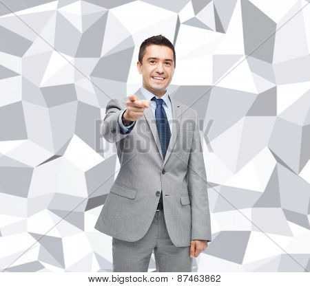 business, people and gesture concept - happy smiling businessman in suit pointing at you over gray graphic low poly background