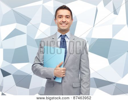 business, people, finances and paper work concept - happy smiling businessman in suit holding folder over gray graphic low poly background