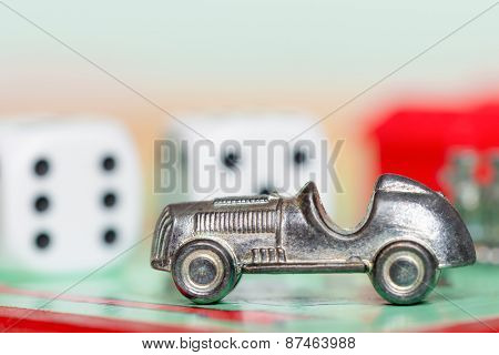 LONDON,UK - APRIL 1,2015 : Car token and dice at the GO space of a monopoly game board