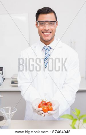 Smiling scientist with protective glasses holding tomatoes in the laboratory