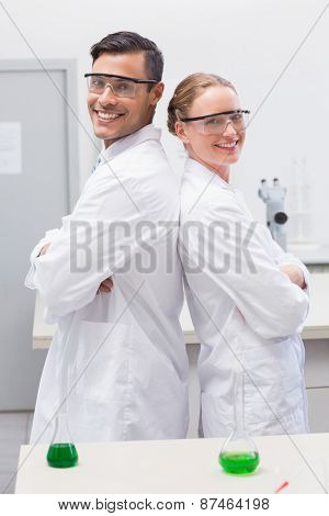 Smiling scientists standing back to back in laboratory