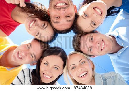 friendship, summer vacation, holidays and people concept - group of smiling friends standing in circle over blue sky