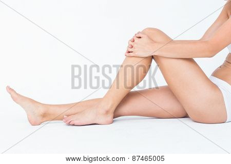 Woman sitting on floor touching her injured knee on white background