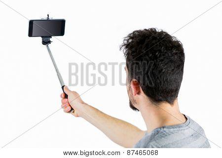 Casual man using a selfie stick shot in studio