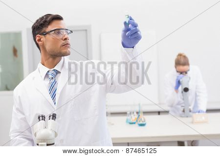 Scientist examining blue precipitate in tube in the laboratory