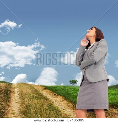 Smiling thoughtful businesswoman against road leading out to the horizon