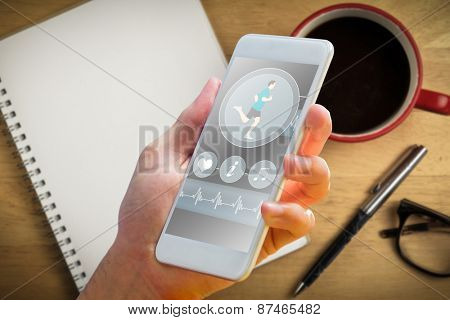 hand holding smartphone against overhead of notepad and pen and coffee