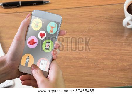 Hand holding smartphone against overhead of office desk