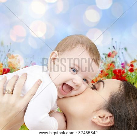 people, family, motherhood and children concept - happy mother hugging adorable baby over blue lights and poppy field background
