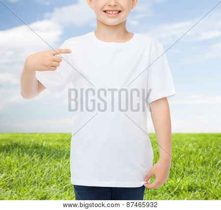 advertising, people, childhood and t-shirt design concept - smiling little boy in white blank t-shirt pointing finger at himself over blue burst rays background