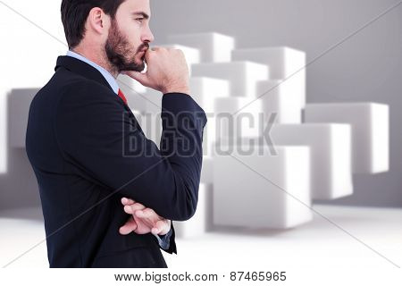 Thinking businessman standing with hand on chin against abstract background