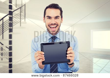 Happy businessman showing his tablet pc against digitally generated room with winding stairs