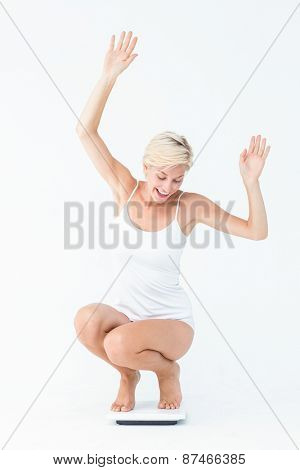 Happy attractive woman crouching on a scales on white background