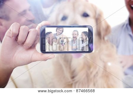 Hand holding smartphone showing against portrait of smiling family sitting together with their dog