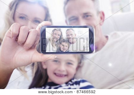 Hand holding smartphone showing against parent cuddling their son on the couch