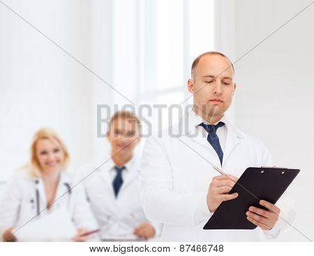 medicine, profession, teamwork and healthcare concept - serious male doctor with clipboard writing prescription over group of medics