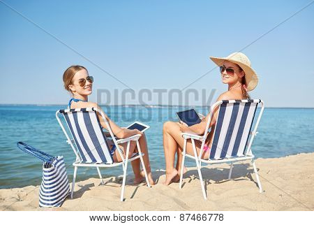 summer vacation, travel, technology and people concept - happy women with tablet pc computers sunbathing in lounges on beach