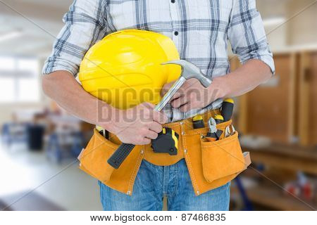 Technician holding hammer and hard hat against workshop