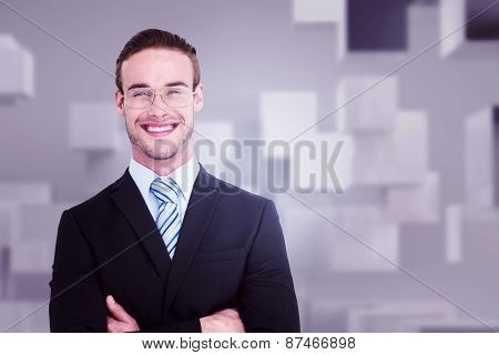 Smiling businessman in suit with arms crossed against abstract white room
