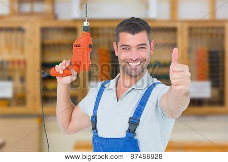 Smiling repairman with drill machine gesturing thumbs up against workshop