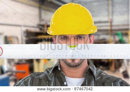 Handyman looking at spirit level against workshop