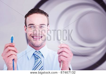 Geeky businessman holding two cables against abstract white room