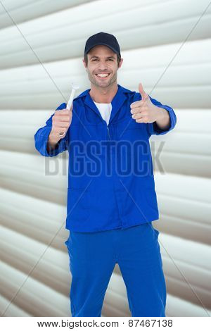 Happy mechanic holding spanner against grey shutters