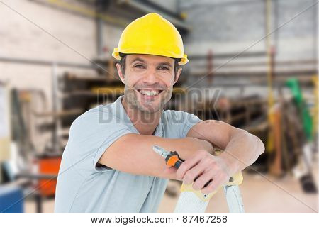 Technician holding pliers while leaning on ladder against workshop
