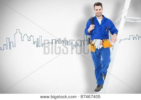 Confident construction worker standing by ladder against grey