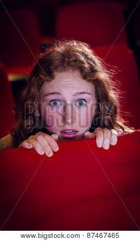 Young woman watching a scary film at the cinema