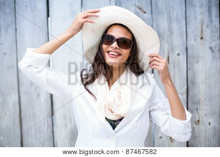 Smiling beautiful brunette wearing straw hat and sun glasses on wooden plank background