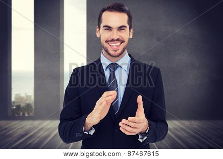 Happy businessman standing and applauding against grey room with windows showing the ocean