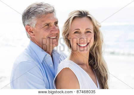 Happy couple standing by the sea and hugging each other at the beach