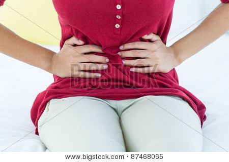 Woman sitting on bed with stomach pain at home