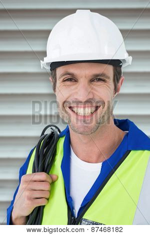 Happy electrician with wire against white background against grey shutters