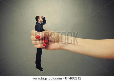 surprised man clamped in big female fist and looking up with misunderstanding against dark background