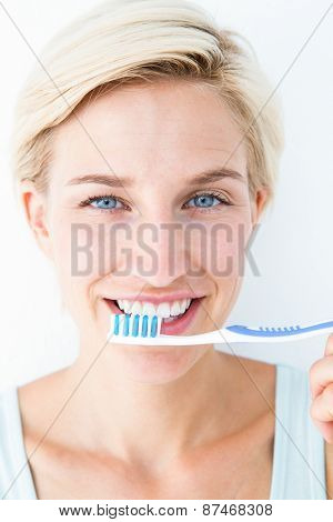 Happy blonde looking at camera holding toothbrush on white background