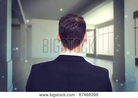Rear view of businessman in suit standing against screen in room with sparks