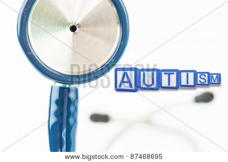 Autism building blocks against part of the blue stethoscope