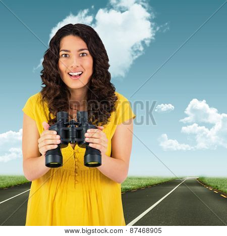 Smiling casual young woman holding binoculars against road leading out to the horizon