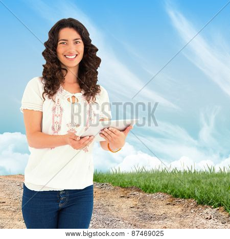 Smiling casual brunette using her tablet pc against road leading out to the horizon