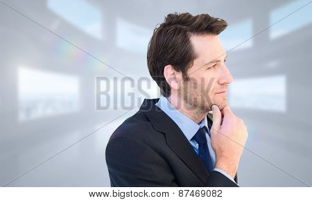 Thinking businessman touching his chin against bright white room with windows